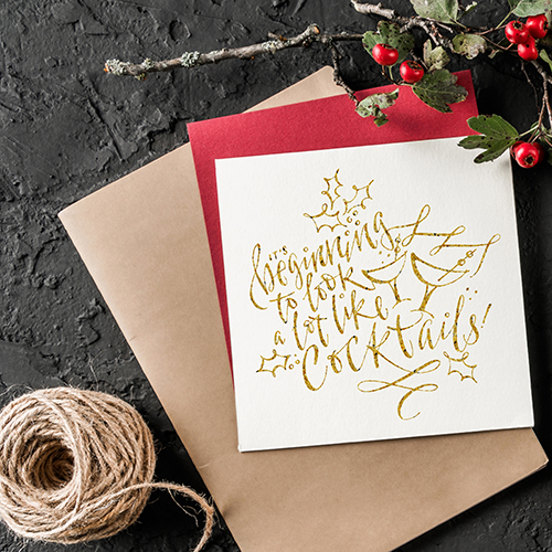 Woman hands making Christmas wreath on dark background with paper card note, pencil, scissors, fir branches and berries. Xmas and Happy New Year card. Flat lay, top view